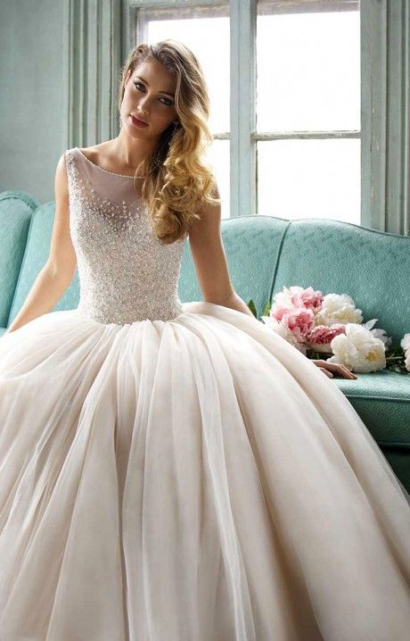 Allure Bridals 9050 is a fairy tale ball gown. This dress features a fully detailed bodice with iridescent and pearlized beading, a sheer, scoop neckline and thin, sheer shoulder straps. The ball gown style skirt features gathering at the waist line, creating a fuller tutu look. It is the perfect ball gown for those spins on the dance floor with the love of your life!