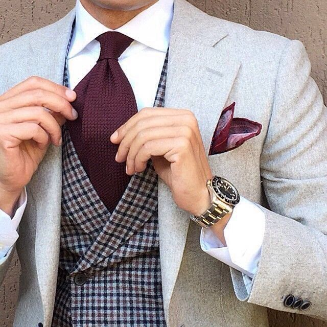 Grey suit, Checkered vest, Purple or Burgundy neck tie & handkerchief, and Gold wristwatch