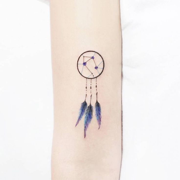 Libra dreamcatcher tattoo on the right bicep.