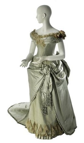 Dress. Worth, 1886, via The Museum of the City of New York: ice blue satin; ice blue uncut ribbed velvet; cream lace; ice blue chiffon; ice blue ball fringe; ice blue beads; artificial flowers; ice blue silk plush Label: Worth / Paris (woven in block letters on petersham).