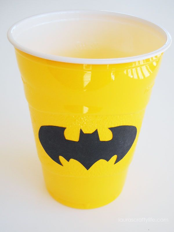 Decorate a plain plastic cup for your party using a cut out shape. This one was used for a LEGO Batman party.