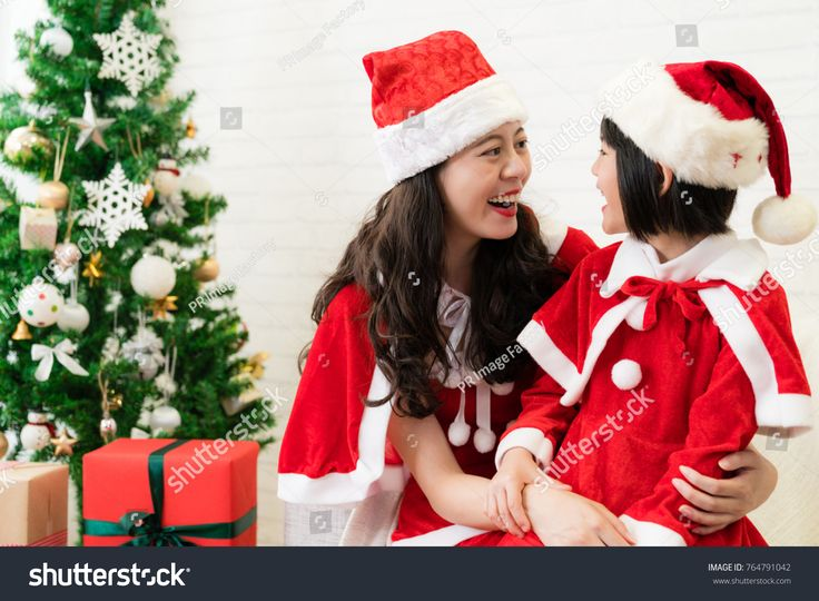 beautiful Asia mother and cute little Asian kid play Santa dress up together sitting on sofa in the living room at home.