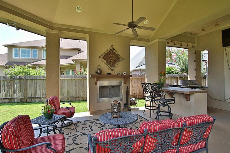 The living space is extended outside with a cozy fireplace, ceiling fan, Bose surround sound, bar, and full outdoor kitchen.