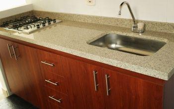 Cocina Integral con mueble bajo color cedro, manijas en acero inoxidable, mesón en granito color Golden Cream y estufa metálica