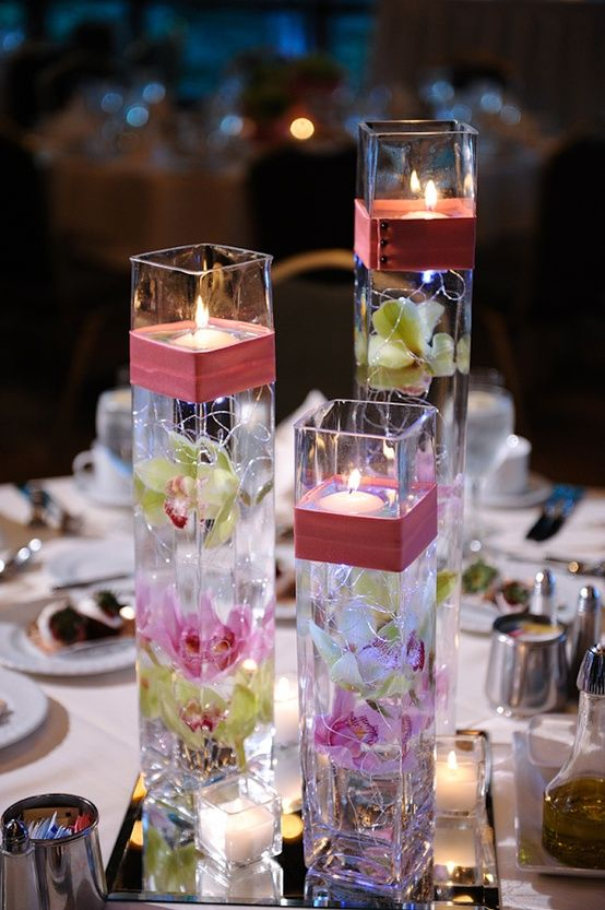Orchid and candle centerpieces. You could do this in your vases, submerged flowers with whispy silver strings, a ribbon and floating candle.
