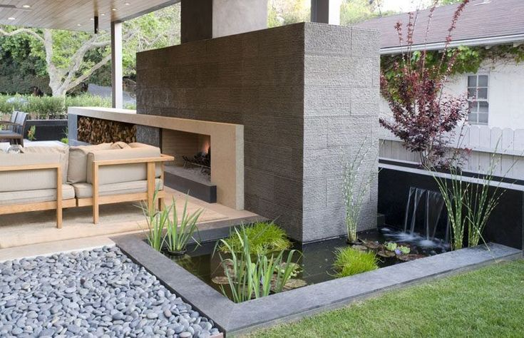 This small pond beside an outdoor lounge and fireplace adds a relaxing touch to the backyard and incorporates water dwelling plants to create a small water garden.
