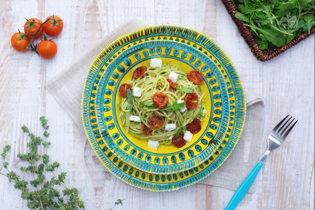 Gli spaghetti integrali con pomodorini confit, feta e pesto leggero di rucola sono un delizioso primo piatto adatto alla bella stagione!