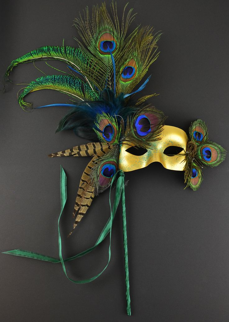Peacock Masquerade Mask    Materials:  71016 - Mask,  38131 - Pheasant Feathers,  38127 - Peacock Feather Picks,  38768 - Peacock Stem.    Sprinkle some glitter on the mask, attach a wooden dowel, and wrap dowel with ribbon! Voila!