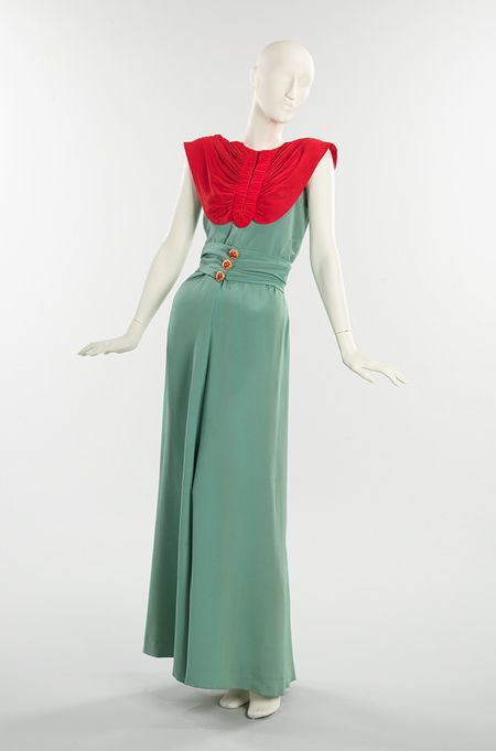 "A lobster-red bodice with crustacean-like shirring combined with marine blue and fish-head motif buttons define the aquatic theme of this evening dress from Schiaparelli's summer 1940 collection. Her new slinky silhouette, called ""the mermaid,"" featured a skirt constricted at the knees before flaring into fullness, as rendered in the a drawing by the Surrealist artist Eleanor Fini published in the March 1940 issue of Harper's Bazaar."