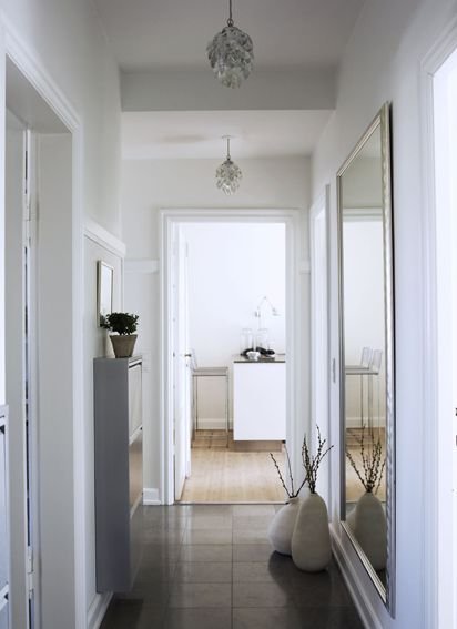 Ultraslim-lined storage unit for shoes in a narrow hallway. A large mirror for that last check-up before heading out also visually extends the space.