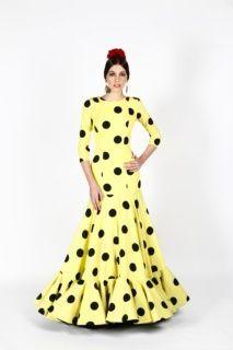Traje de flamenca de popelín amarillo con lunares negros, escote delantero a la caja y trasero en V con falda de capa con un volante ancho y talle alto .