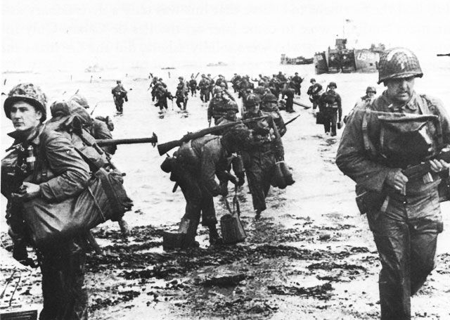 This was photographed shortly after the high-casualty victory at Omaha Beach. At a closer look, you might see the soldiers' weary faces and broken spirits. -Omaha Beach, France, June 1944