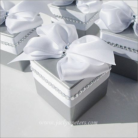 Our luxurious silverfavor boxes are perfect to package wedding or 25th anniversary party treats. Each arrives fully assembled with a hand made bow and silver rhinesstones. Just fill with your candy!    Set Of 12 fully decorated and assembled one piece boxes.   Each measures 2 x 2 x 2   We hand accent each one with a luxury satin handmade bow and silver rhinestones.   Holds 1 regular macaron, 70 small chocolates or mints, 50 classic jordan almonds, 1 truffle or two gourmet tea bags - just to…