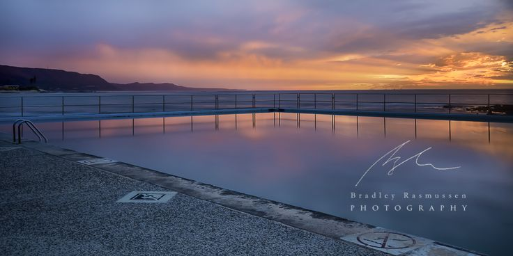 On this particular morning there was a bit of rain about, but the rising sun would not be discouraged. The sunlight pushed through the clouds like an apocalyptic movie scene.  The beautiful light created by the sun bursting through the clouds,and  shining  through the rain was beautiful and soft.  #Seascape #ocean #Pool #Sunrise  #NSW #Illawarra http://www.bradleyrasmussenphotography.com.au https://www.facebook.com/bradleyrasmussenphotography
