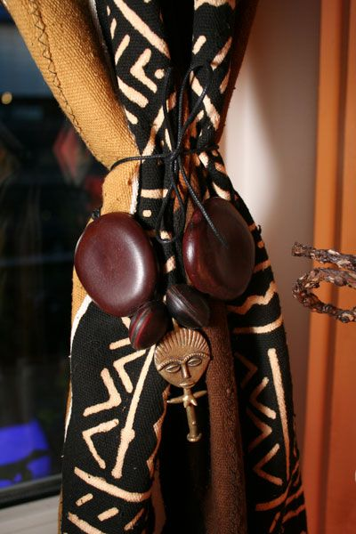 I not only luv the use of African mud cloth as curtains, but the organic African ornaments used as a tie back is great!