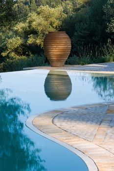 Terracotta Urn reflected in Swimming Pool, Gina Price's garden in Corfu, photographed by Clive Nichols