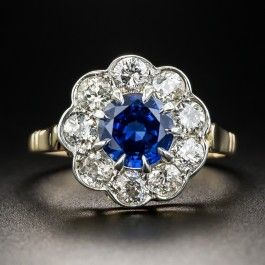 A radiant royal blue round faceted sapphire, weighing 1.51 carats, is encircled by a sparkling scalloped halo composed of bright white European-cut diamonds in this classic vintage jewel hand-fabricated in platinum over 18K yellow gold. 1/2 inch, currently ring size 7 1/2.