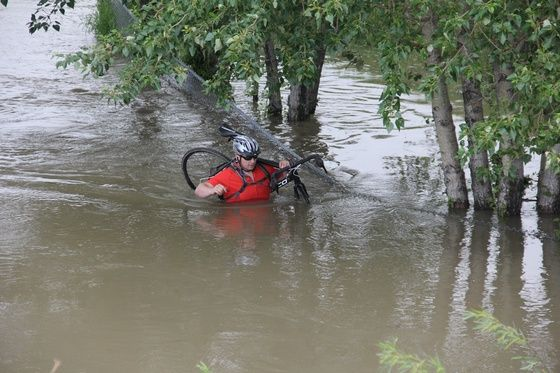 If this guy is biking in flood zones , he needs a life jacket to go with his helmet. Calgary Floods 2013
