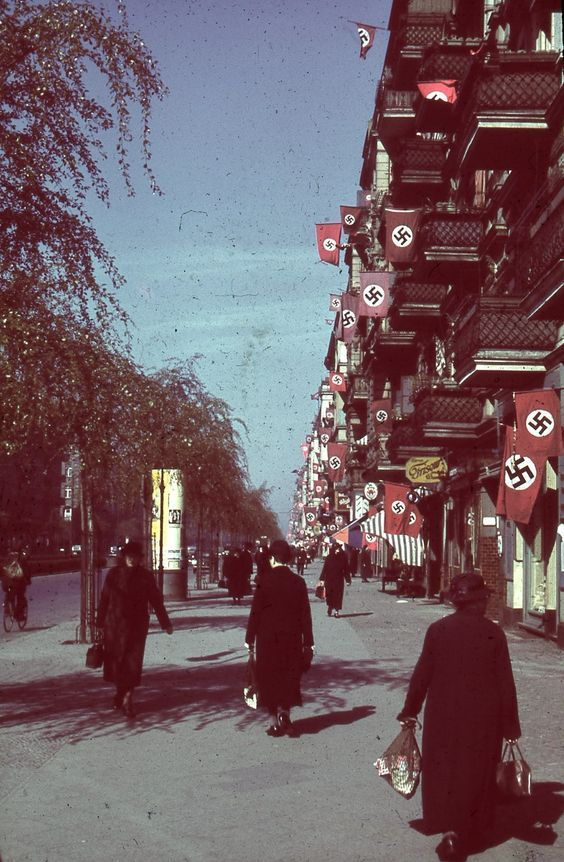 German citizens carry about their day as they walk along the flag-filled avenue during a sunny afternoon in the Reich.