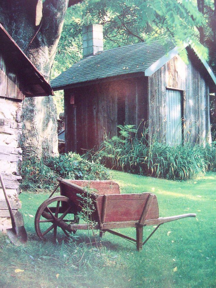 Love the weathered wood & the old wheelbarrow