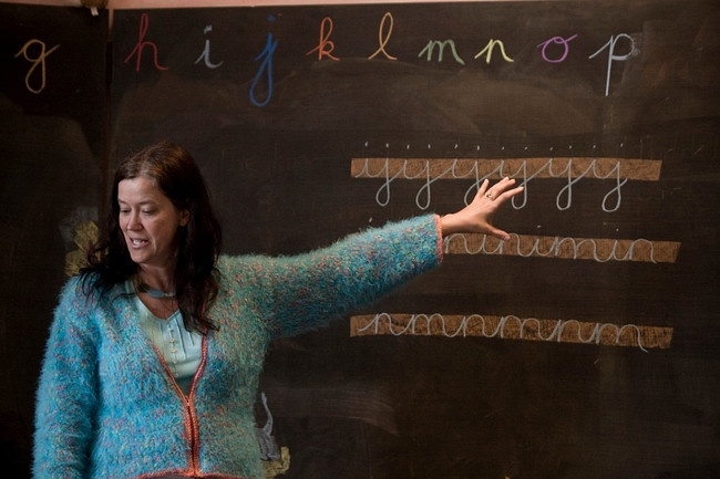 A teacher explaining lettering and the alphabet on a blackboard to pupils writing at the Moray Rudolf Steiner School, Forres, Scotland during a lesson. The school was established in 1986 and founded on the principles of Austrian philosopher Rudolf Steiner (1861-1925) who established a network of schools based on his teachings which has spread to around 60 countries worldwide. The first of over 1000 of Steiner's Waldorf schools was founded in 1919 in Stuttgart, Germany and became one of the…