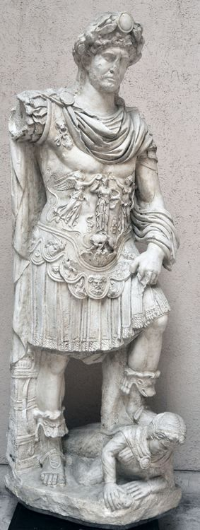 Hadrian as imperator, from Hierapytna, Greece, c. 120-125 AD, marble. Cuirass, paludamentum, boots, elaborate wreath. Cuirass depicts 2 Vics crowning Minerva/Athena who stands on R and R she-wolf. Triumph of Greece and Rome under a united empire against barb. world, symbolised by enemy under left foot. Trampling motif originates with TJ in equestrian form.