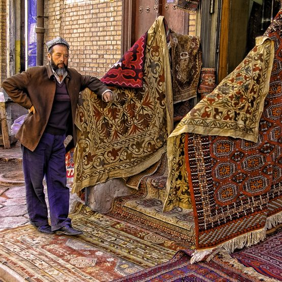 A carpet seller waits for customers outside his shop on an old lane in Kashgar.