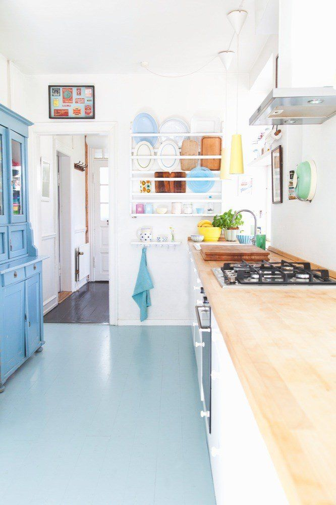 pale aqua painted floor looks good in this white kitchen with light butcher block counter tops.