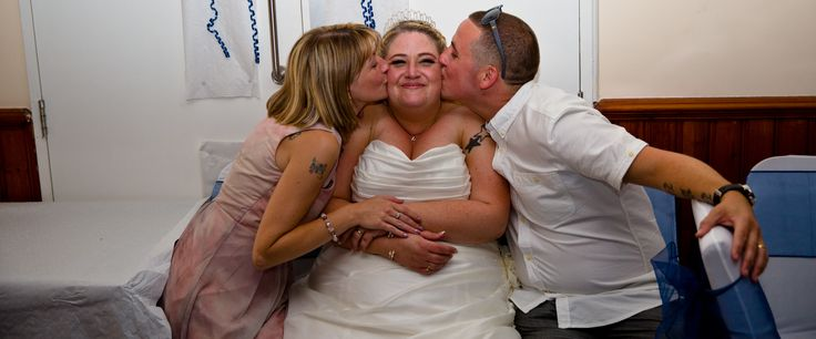 Wedding photography showing the bride receiving a BIG Kiss from tow of her best friends AGV club Acton.