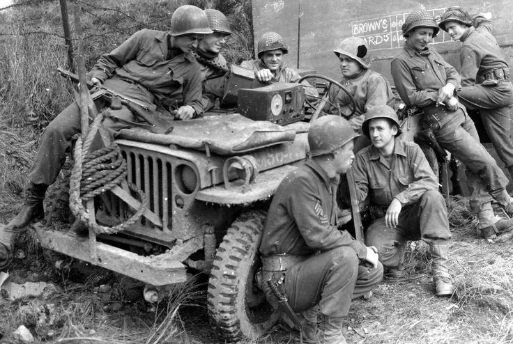 Downtime in WWII. Soldiers by a Jeep, listen to a game on the radio.