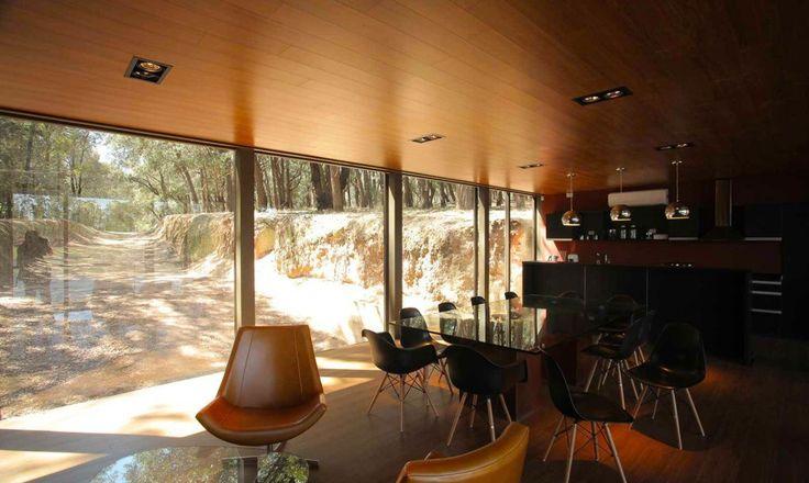 Кухня и столовая в доме отделаны панелями темного дерева. .