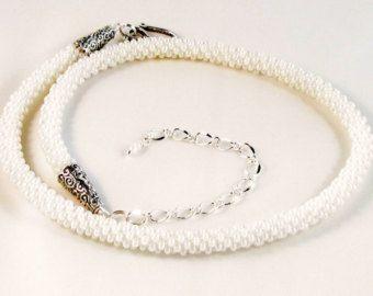 Semplice eleganza è trovato in questo braccialetto perline kumihimo. Ho fatto questo braccialetto utilizzando lantica tecnica di intrecciatura di kumihimo. Otto fili di calza di cavo sono stati intrecciati su un disco. Ogni piccolo branello è trascinato separatamente nella treccia ogni volta che un cavo viene spostato. Ho usato il vetro perle seme beeds dimensioni otto per creare questo braccialetto corda perla classico. Il bracciale è completato con coni placcati argento chiusura aragosta…