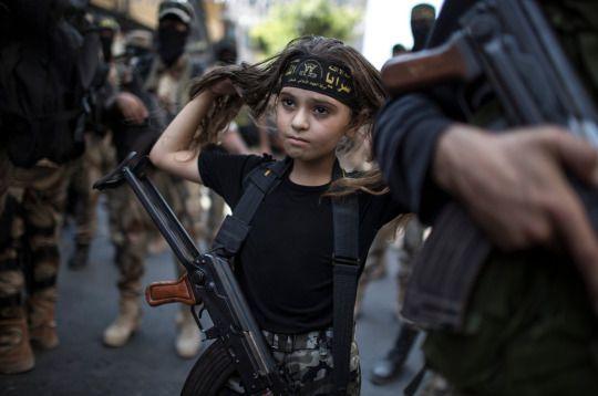 A Palestinian girl with a Kalashnikov rifle, amid Islamic Jihad militants in Gaza City.