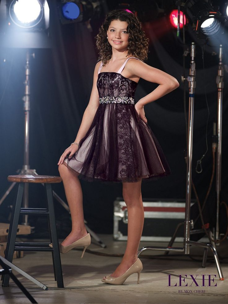 This short Lexie by Mon Cheri TW11516 sleeveless junior party dress features a lace bodice with straight neckline and charmeuse shoulder straps. A beaded band cinches the waistline. The charmeuse A-line skirt has a gathered tulle overlay with lace insets and finishes in an above the knee hemline.