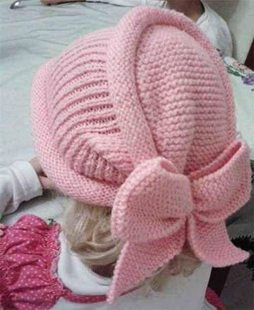 Симпатичная теплая шапочка для девочки, связанная спицами. Описание вязания 1 деталь: Набрать на прямые спицы число петель равное окружности головы. 10 рядов чулочной вязкой. 30 рядов резинка 1×1. 10…