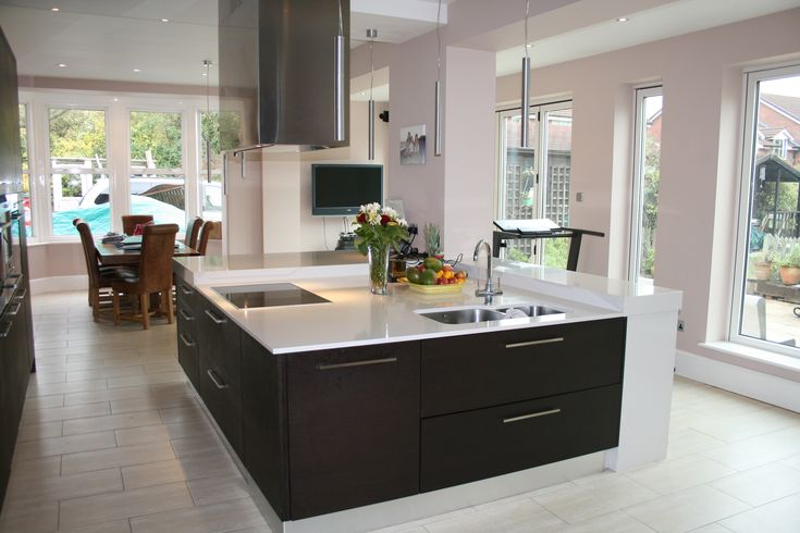 Large contemporary square kitchen island built to incorporate a structural pillar. Island design has hob, sink, storage and raised seating bar area along two sides of the island.