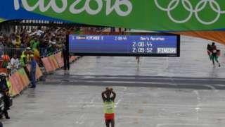 Image copyright                  AP Image caption                                      Feyisa Lilesa cuando se aproximaba a la meta.                                El gesto que hizo al acercarse a la meta en el maratón olímpico es considerado uno de los momentos más políticos de Río 2016 y la razón por la que Feyisa Lilesa sigue en Brasil.   6 gestos que marcaron las Olimpiadas de Río 2016  Y es que, según el corredor etíope ganador