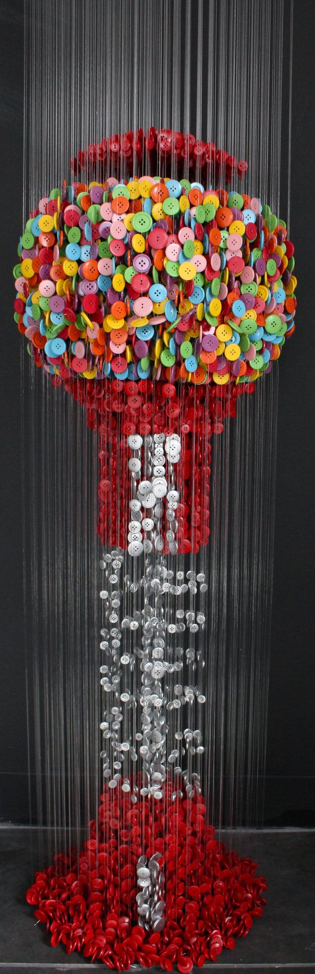Miami-based artist Augusto Esquivel realistically duplicates objects by suspending thousands of sewing buttons on mere strings. Each strand of his incredible sculptural pieces work with their adjacent string of buttons to create colorful replicas of everything, from a basic geometric cube to a stone fountain covered in flowers and spouting water.