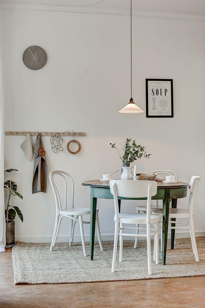 Un coin repas au style champêtre avec sa table en bois verte et ses chaises de bistro