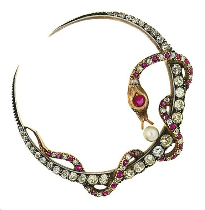 A late 19th century diamond, ruby, synthetic ruby, paste and cultured pearl brooch  Modelled a graduated old brilliant-cut diamond crescent with entwined old-cut diamond and vari-cut ruby and synthetic ruby serpent with green paste eyes, and later single cultured pearl accent, mounted in silver and gold, circa 1890
