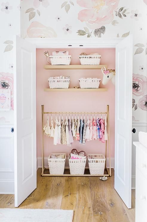 Wood panel floors lead to white double doors, surrounded by wainscoted lower walls and Jolie Wallpaper covered upper walls, that open to a pink nursery closet boasting a three white storage baskets sat on the floor underneath a brass clothes rack by Such Great Things that's positioned underneath three floating shelves holding smaller white wicker baskets while a unicorn peaks out from the corner.