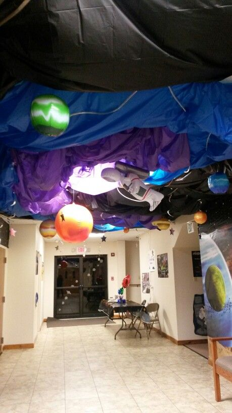 This is out foyer for the To the Edge space themed Bible school. Decorations were done with tablecloths, rope lights and loads of hanging things.