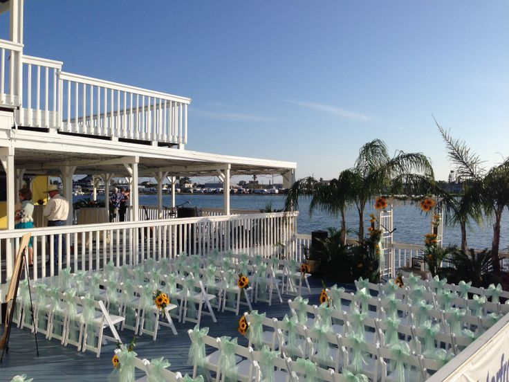This set up is at The Waterfront Event Center on the lower Deck.  The Upper Deck is used for Cocktail Hour.  This is quickly becoming the GoTo wedding venue if you want to be over the water.  It's the only one in Galveston.   Chopin Mon Ami Catering & Cakes