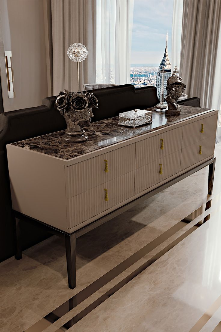 A high gloss cappuccino lacquered structure with feature deco style ribbed drawers, statement metal droplet handles in an antiqued gold finish with a perfectly contrasting top insert in the finest polished Emperador dark marble. The Art Deco Inspired High End 6 Drawer Buffet Sideboard, Classic Art Deco inspiration meets timeless glamour. A touch of sophistication and opulence, creating the most striking of outlines which is perhaps one of the most recognisable features of Art Deco.