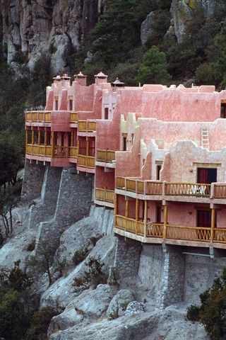 Hotel Posada Mirador, Copper Canyon, Chihuahua, México. Poised like an eagle's nest at the canyon's edge, is the Posada Barrancas Mirador Hotel, near the highest point of the canyon. Overlooks exhibit awe-inspiring scenery from the rim of Copper Canyon. This deluxe hotel is surrounded by pine trees, and appears to be etched out of the natural rock itself. (V)