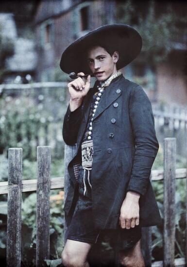 1929年、オーストリア、シュタイアーマルク州でドイツ人写真家Hans Hildenbrandによって撮影されたパイプを吸う若い男性のカラー写真。 南ドイツと同様にレーダーホーゼンと呼ばれる革製の半ズボンを身に着けている。