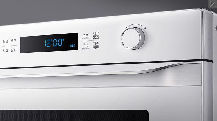 회색 빛의 배경에 흰색 색상의 삼성 직화오븐의 오른쪽 상단부분이 확대되어 나타나 있습니다. 제품의 상단에는 사용버튼과 온도조절 다이얼이 위치해 있습니다.