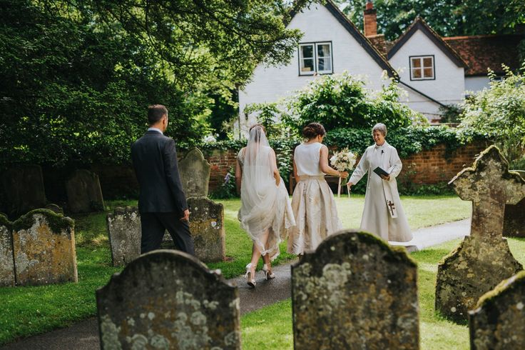 The bridal party make their way to the back of Rotherwick Church to meet the vicar. Photo by Benjamin Stuart Photography #weddingphotography #bridalparty #churchwedding #letsgogetmarried #bride