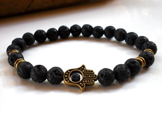 Mens bracelet. Hamsa Lava bracelet for men and women. This bracelets features 8mm black Lava rock gemstone beads complemented with a bronze plated Hamsa hand all strung with strong elastic clear thread. It can be made with Hamsa and metal accents in silver plated, just buy it and let me a note to seller at checkout with instruccions.  Get all the benefits of this protective gemstone wearing this bracelet. The elemental powers of fire and earth, lava rocks are rich in minerals from deep in…