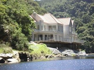 The perfect 'lock-up and go' paradise home. This immaculately designed, contemporary double story home is sheltered by ancient Yellowwood and Milkwood trees on the banks of the Kaaimans River. Comprising open plan living areas with vast windows inviting the natural surroundings right into your home. Stack doors open onto a covered patio with built-in braai and a cantilevered deck overlooking the river, lush trees, dramatic rock faces and overhanging natural gardens.